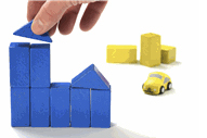 plain wooden blocks arranged in the shape of a building, a hand reaches in to place the final block to complete the building