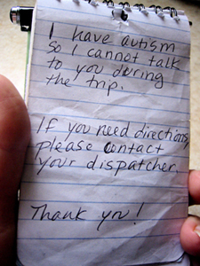 closeup of a hand holding a small notepad, on the notepad is written, 'I have autism so I cannot talk to you during the trip. If you need directions please contact your dispatcher.  Thank you!'